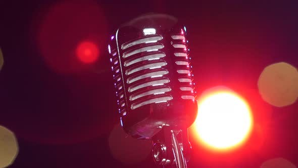 Cover Image for Retro Shiny Microphone Rotating Against Blurry Flashing Lights. Close-up