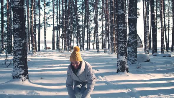 Портрет красивой молодой женщины в зимнем лесу веселая девушка бросает снег и смотрит на