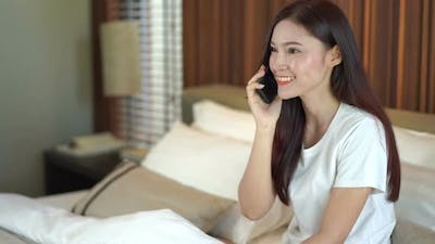 woman talking on mobile phone on bed