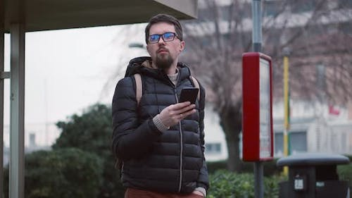 Citizen Waits for Bus at Stop Holding Smartphone