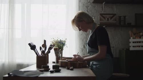 Woman Carpenter Drawing Markup with a Pencil on a Piece of Wood