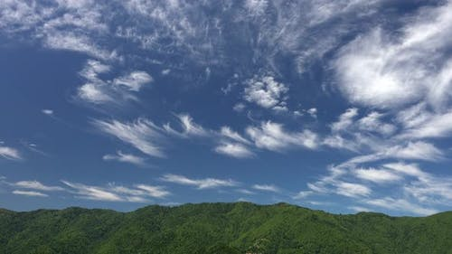 Partly Cirrus Cloud on Forested Mountain Ridge in Blue Sky