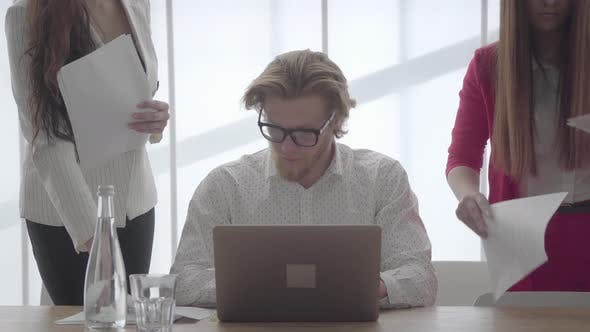 Cover Image for Portrait Successful Blond Man in Glasses Sitting in a Light Comfortable Office with Netbook at the