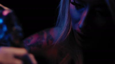 Close up of a young female tattoo master tattooing in her studio. BMPCC 4K