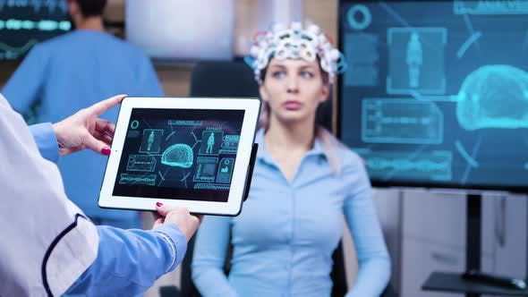 Female Doctor Looking at Tablet with Patient Brain Activity