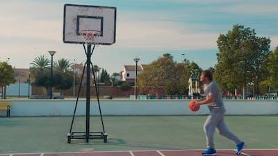 Basketball Player Training. Playing on Basketball Field. Basketball Player Bouncing with the Ball.