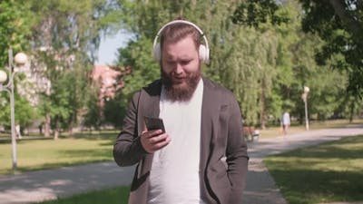 Man Listening to Music and Walking in Park