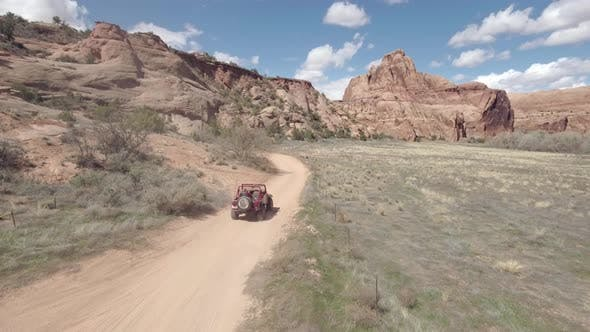 Thumbnail for Aerial drone view of a 4x4 vehicle driving off-road on a dirt road in Moab, Utah.