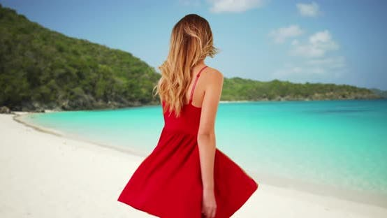 Thumbnail for Happy millennial girl in red dress laughing and dancing on the beach on sunny day