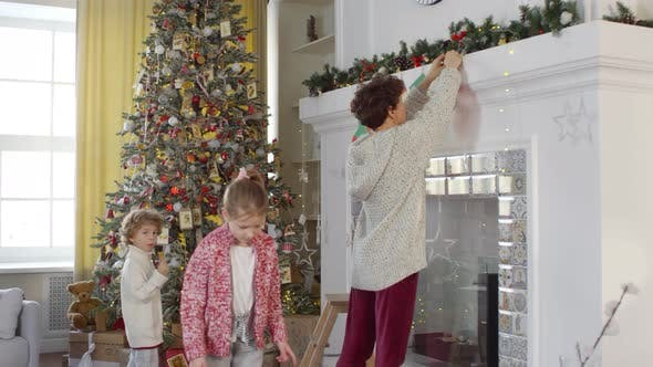 Thumbnail for Children Helping Mom to Decorate Fireplace with Christmas Stockings