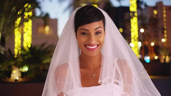 Thumbnail for Beautiful black female in wedding dress laughing at camera outdoors in evening