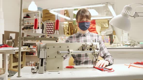 Seamstress Sitting at Workplace and Sewing Medical Mask