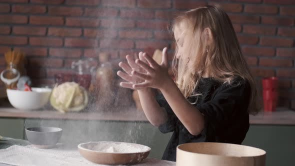 Cover Image for Young Girl Is Clapping Hands in Flour in a Kitchen