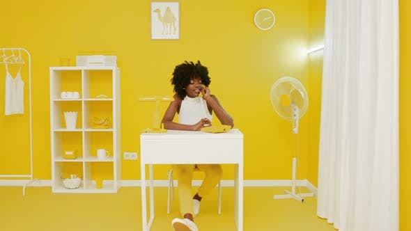 Happy Woman Has Phone Talk In Yellow Office