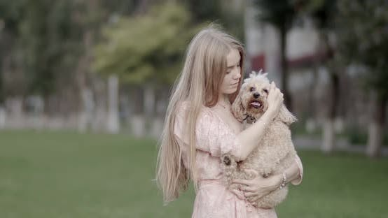 Thumbnail for A beautiful girl, blonde, is holding a poodle dog in her hands