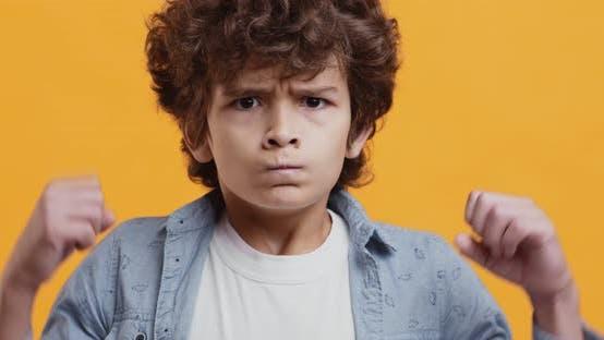Wütender kleiner Junge runzelte Kamera und ballte Fäuste an die Kamera