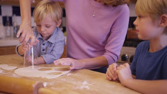 Thumbnail for Beautiful caucasian mother cutting round cookie shapes with two sons