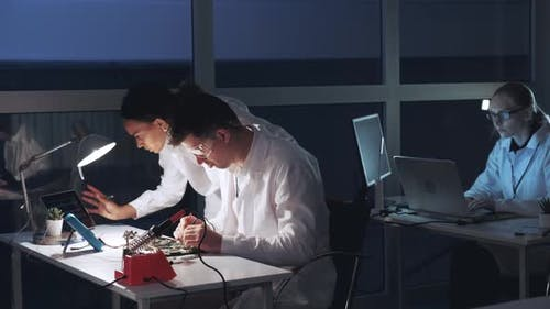 Two Mixed Race Engineers Checking Motherboard with Multimeter Tester