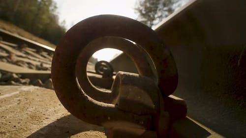 A Macro Shot of the Rails of a Railroad Track Through the Fasteners on Sunset Background