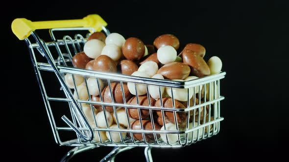 Thumbnail for Peanuts in Black and White Chocolate Are in a Small Shopping Trolley