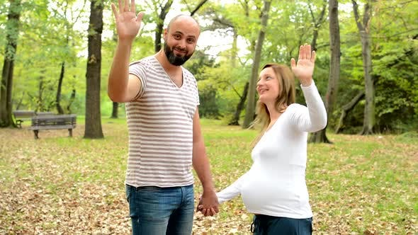 Thumbnail for Handsome Man and Young Happy Pregnant Woman Smile To Camera and Wave with Hands