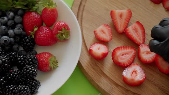 Thumbnail for Chef in Black Gloves Slicing Fresh Strawberry on Wooden Cutting Board. Close Up Top View