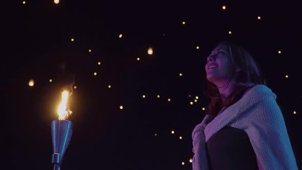 Thumbnail for Woman watches as sky lanterns fly Into the night sky
