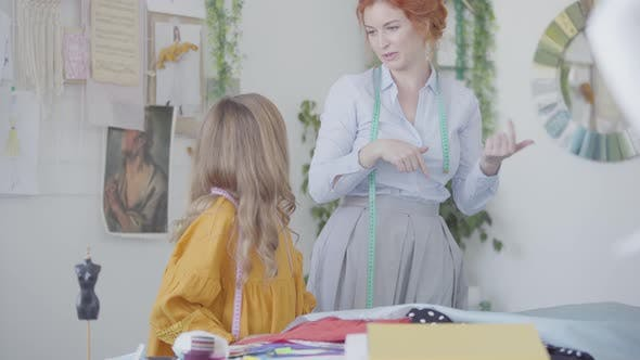 Thumbnail for Red-haired Mother and Her Daughter Admiring a Piece of Beautiful Fabric