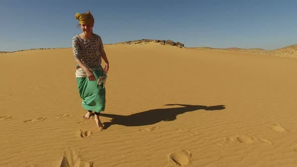 Thumbnail for Happy woman dancing barefoot in desert, Egypt