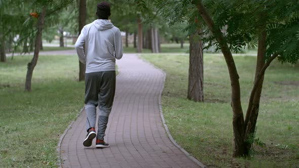 Thumbnail for Rear View of African Man Jogging at Summer Day