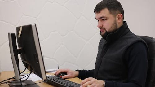 Young bearded office worker man working behind desk on computer