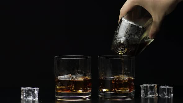 Pouring Whiskey, Cognac Into Glass. Black Background. Pour of Alcohol Drink