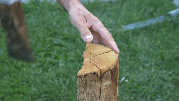 Thumbnail for Old man chopping firewood. Man with axe chops firewood log.