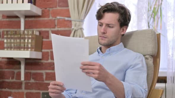 Thumbnail for Disappointed Young Man Reading Documents