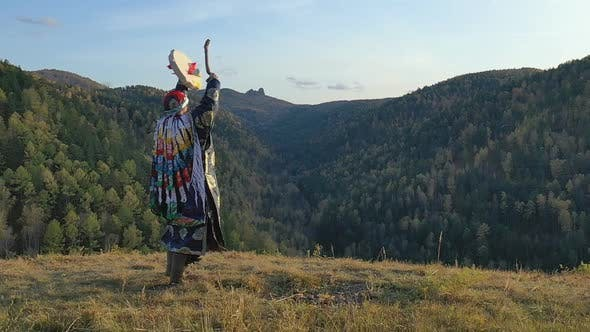 Thumbnail for Siberian Shaman Performs a Ritual Dance and Beats a Tambourine on the Top of the Mountain.