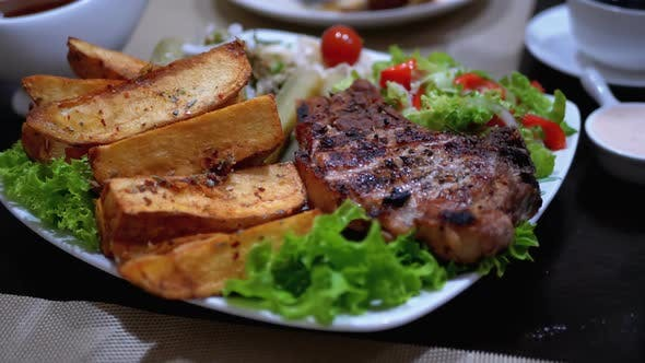 Thumbnail for Steak on Ribs with Potatoes and Salad on a Table in a Georgian Restaurant