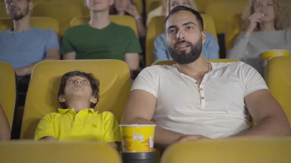 Cheerful Middle Eastern Man and Boy Watching Film in Cinema and Talking. Portrait of Happy Father