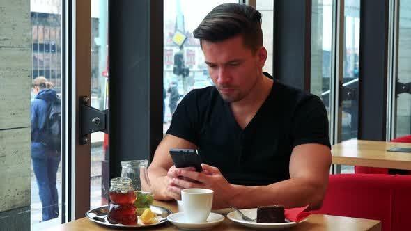 Thumbnail for A Young Handsome Man Sits at a Table with Meal in a Cafe and Works on a Smartphone