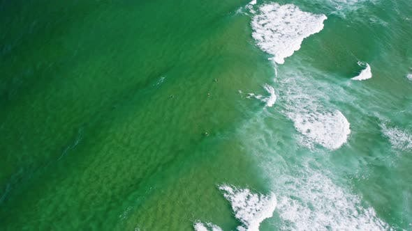 Thumbnail for Aerial View of Waves of Emerald Green Ocean Rolling Towards the Shore. Unrecognized Surfer Trying To