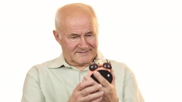 Thumbnail for Old Man Looking at an Alarm Clock Smiling To the Camera