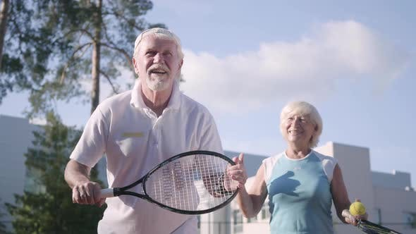 Thumbnail for Adult Couple Playing Tennis on a Sunny Day
