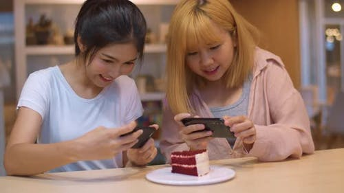 young Asia friend using phone taking a photograph food and cake at coffee shop.