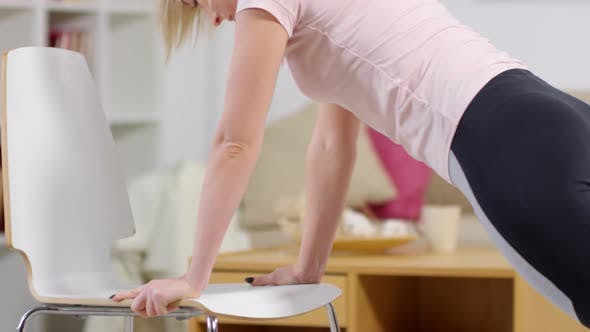 Cover Image for Fit Woman Doing Push-Ups on Chair at Home