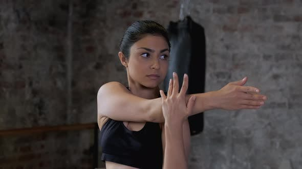 A Young Indian Athletic Female Stretching Hands Demonstrate Flexible Body at Gym