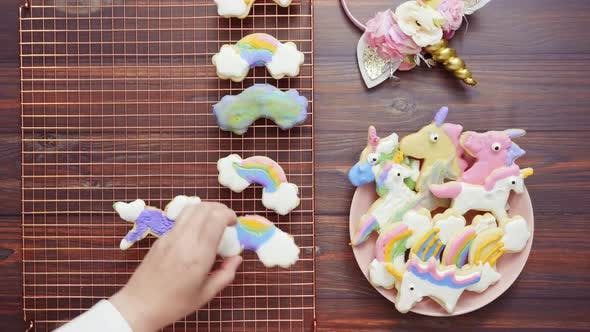 Thumbnail for Unicorn cookies decorated with royal icing drying on drying rack.