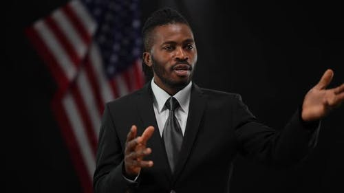 Persuasive Confident African American Man Talking and Gesturing with Blurred US Flag at Black