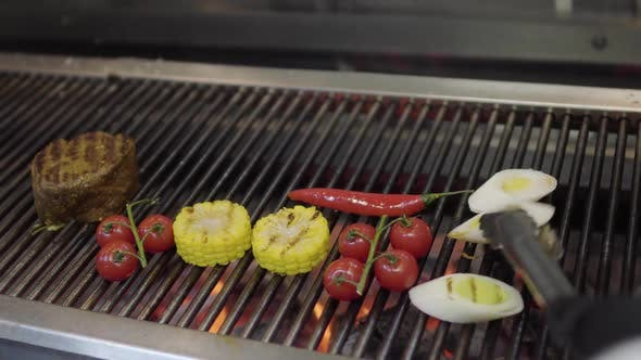 Cover Image for Unrecognized Chef Cooking Vegetable on the Grill in the Restaurant Kitchen Close-up. Meat, Corn