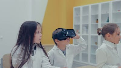 Little Children in the Classroom Watching in Virtual Reality Glasses