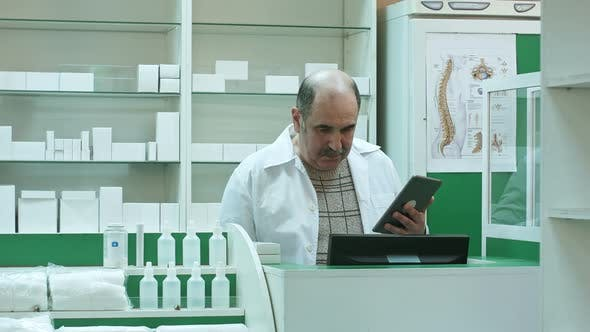 Thumbnail for Senior Pharmacist with Mustache Working on Tablet Pc Checking Medicine in Pharmacy