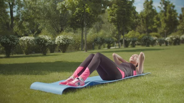 Fit Woman Training Abs on Sports Mat in City Park